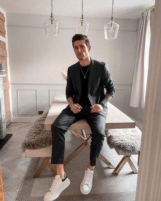 Charcoal Suit Outfits In Their 20s: If the occasion calls for an effortlessly classy ensemble, you can easily rely on a charcoal suit and a black crew-neck t-shirt. For a modern hi/low mix, complement your look with white and black leather low top sneakers. Rock this combo to show the world your maturity even as a guy in his 20s.