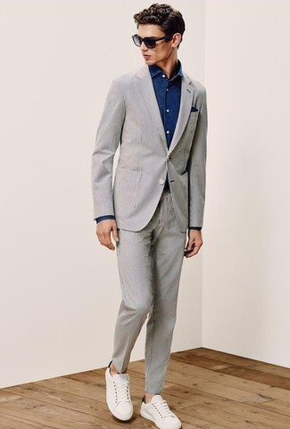 How to wear: grey seersucker suit, navy denim shirt, white leather low top sneakers, navy pocket square