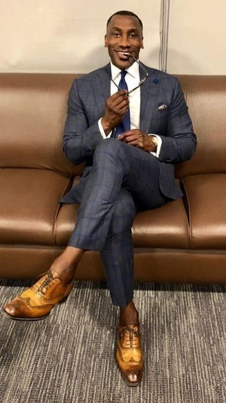 How to Wear a Beige Pocket Square: Rock a navy check suit with a beige pocket square for standout menswear style. Let your sartorial sensibilities truly shine by finishing off this look with a pair of tobacco leather brogues.