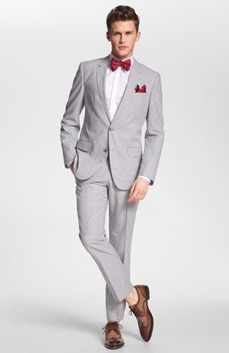 Red Polka Dot Bow-tie Outfits For Men: This relaxed casual combo of a grey suit and a red polka dot bow-tie is ideal if you need to feel confident in your ensemble. Put an elegant spin on an otherwise too-common look with brown leather derby shoes.