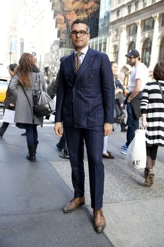 How to Wear a Navy Vertical Striped Suit: Putting together a navy vertical striped suit and a white dress shirt is a surefire way to inject your closet with some rugged elegance. For extra fashion points, enter brown leather derby shoes into the equation.