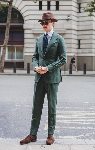 How to Wear a Dark Green Suit: A dark green suit and a white dress shirt are a sophisticated getup that every modern guy should have in his collection. You can get a little creative when it comes to footwear and introduce brown suede loafers to the equation.