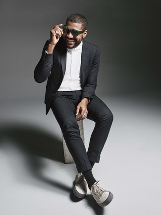 How to wear: black suit, white dress shirt, grey leather low top sneakers, dark green sunglasses