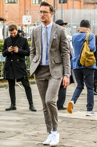 How to Wear a Light Blue Vertical Striped Dress Shirt For Men: This look suggests it pays to invest in such timeless menswear pieces as a light blue vertical striped dress shirt and a brown vertical striped wool suit. Add a mellow vibe to this ensemble by sporting a pair of white low top sneakers.