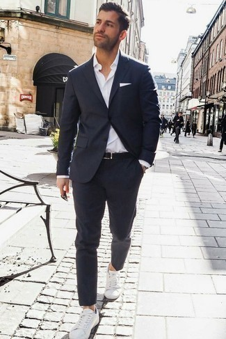 How to Wear a Navy Suit: A navy suit and a white dress shirt are a polished combo that every sharp guy should have in his sartorial collection. If you wish to instantly dress down this getup with shoes, introduce white low top sneakers to the mix.