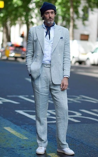 How to Wear a Light Blue Suit: Teaming a light blue suit and a white dress shirt is a surefire way to inject personality into your day-to-day rotation. Shake up your getup by finishing off with a pair of white leather low top sneakers.