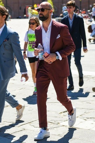 How to Wear a Burgundy Suit: This is indisputable proof that a burgundy suit and a white dress shirt are amazing when matched together in a classy look for a modern guy. A pair of white and black canvas low top sneakers will add an easy-going vibe to this look.