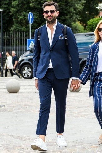 How to Wear a Bracelet For Men: This laid-back pairing of a navy suit and a bracelet is a foolproof option when you need to look stylish but have no extra time. Complement your outfit with white leather low top sneakers et voila, this getup is complete.