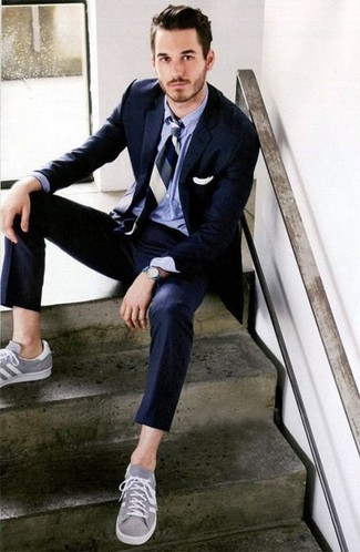 How to Wear a Blue Watch For Men: The combination of a navy suit and a blue watch makes for a neat relaxed casual outfit. The whole ensemble comes together if you introduce grey low top sneakers to the equation.