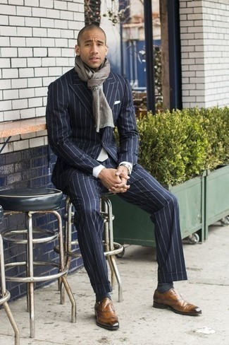 How to Wear a Navy Vertical Striped Suit: Wear a navy vertical striped suit and a white dress shirt - this look is bound to make a statement. When not sure as to what to wear when it comes to footwear, go with a pair of tan leather monks.