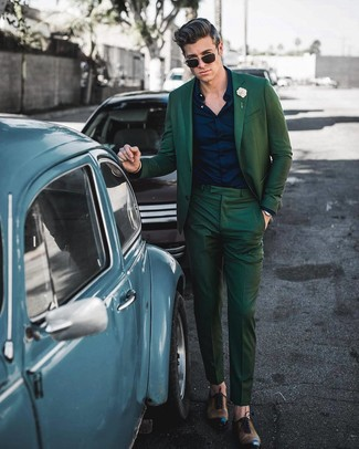 How to Wear a Dark Green Suit: A dark green suit looks so polished when worn with a navy dress shirt in a modern man's look. Let your outfit coordination credentials truly shine by finishing off this getup with brown leather oxford shoes.