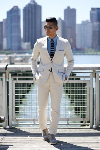 How to Wear a White Suit: This pairing of a white suit and a light blue chambray dress shirt is a goofproof option when you need to look polished and incredibly dapper. A pair of grey suede oxford shoes finishes this outfit very nicely.