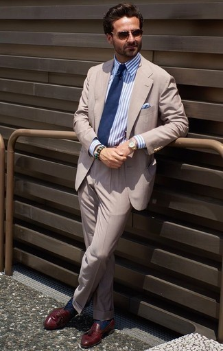 How to Wear Burgundy Leather Tassel Loafers: Wear a beige suit with a white and blue vertical striped dress shirt to look smooth and classic. When it comes to footwear, introduce burgundy leather tassel loafers to this outfit.