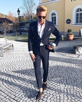 1200+ Dressy Outfits For Men: Wear a navy suit and a white dress shirt to look modern and smart. Go ahead and introduce dark brown suede tassel loafers to your look for a more laid-back aesthetic.