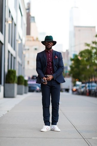 How to Wear a Navy Vertical Striped Suit: A navy vertical striped suit and a burgundy long sleeve shirt worn together are a match made in heaven for gents who prefer sophisticated combos. Ramp up the style factor of your ensemble by sporting a pair of white and red canvas high top sneakers.