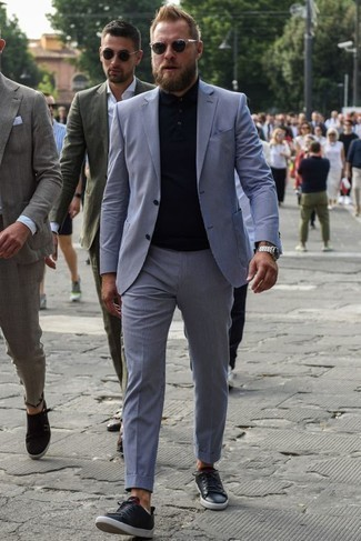 How to Wear a Light Blue Suit: This pairing of a light blue suit and a black polo is a fail-safe option when you need to look casually sleek in a flash. Loosen things up and add a pair of black leather low top sneakers to the mix.
