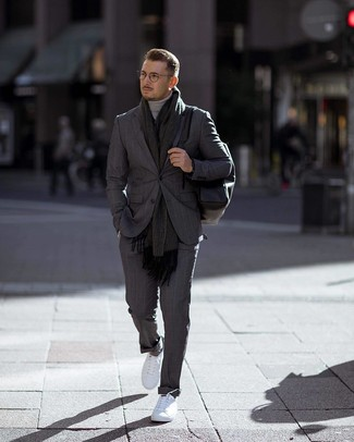 How to wear: charcoal vertical striped suit, grey turtleneck, white low top sneakers, black leather backpack