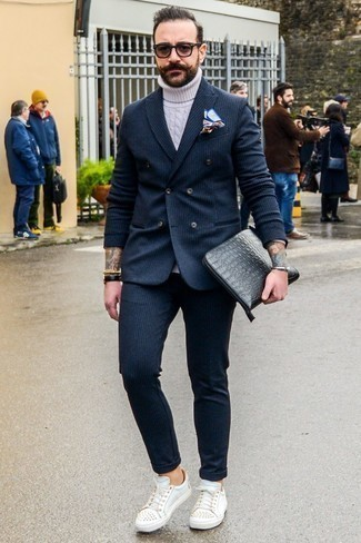 How to Wear a Black Leather Zip Pouch For Men: A charcoal vertical striped suit and a black leather zip pouch? This is an easy-to-achieve ensemble that any gentleman could rock a version of on a daily basis. The whole outfit comes together when you complement this outfit with white studded leather low top sneakers.
