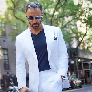 How to wear: white suit, navy v-neck t-shirt, navy and white polka dot pocket square, navy sunglasses