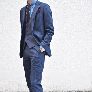 How to wear: navy vertical striped suit, navy waistcoat, blue chambray dress shirt, dark brown tie