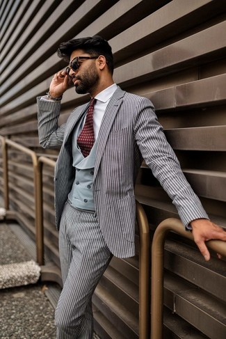 How to wear: grey vertical striped suit, grey waistcoat, white dress shirt, burgundy print tie