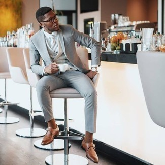How to Wear a Suit: This polished pairing of a suit and a grey plaid waistcoat is a popular choice among the fashion-savvy chaps. Tan leather monks will add a more casual finish to an otherwise traditional look.