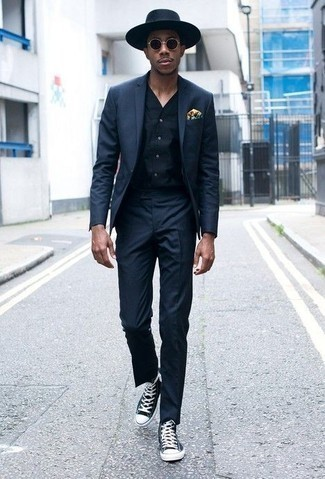 How to Wear a Navy Suit: This pairing of a navy suit and a navy waistcoat can only be described as ridiculously dapper and polished. A trendy pair of navy and white canvas high top sneakers is the simplest way to inject a dash of stylish casualness into your look.