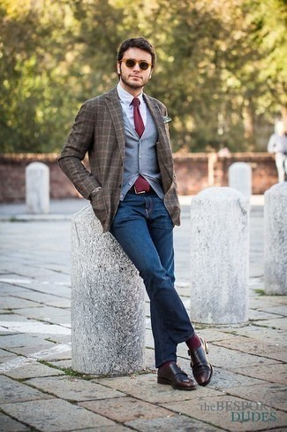 How to Wear a Burgundy Tie For Men: This combination of a grey sweater vest and a burgundy tie will add powerful essence to your look. Introduce a pair of dark brown leather double monks to the equation to infuse a sense of stylish nonchalance into this outfit.