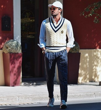 How to wear: beige sweater vest, light blue long sleeve shirt, navy vertical striped chinos, white print canvas low top sneakers