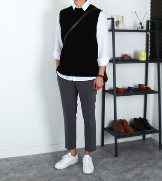 How to Wear a Bag For Men: One of the most popular ways for a man to style out a black sweater vest is to team it with a bag in a casual outfit. The whole ensemble comes together brilliantly if you complete this ensemble with a pair of white leather low top sneakers.