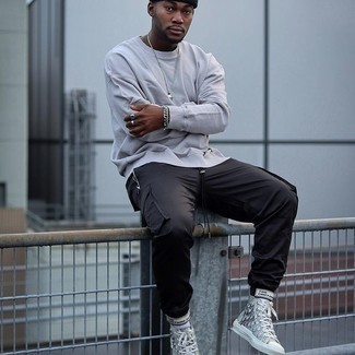 Grey Sweatshirt Outfits For Men In Their 20s: Combining a grey sweatshirt with black cargo pants is a savvy idea for a casual yet on-trend look. Finishing off with a pair of grey print canvas high top sneakers is a guaranteed way to bring a more laid-back aesthetic to this look. Wondering how to nail casual style as you cruise through your 20s? This pairing is the perfect answer.