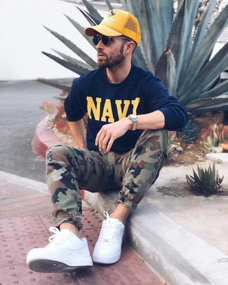 How to wear: navy print sweatshirt, olive camouflage cargo pants, white leather low top sneakers, yellow baseball cap