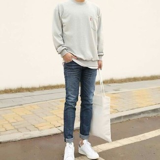 How to Wear a Grey Sweatshirt In Your 20s For Men: This pairing of a grey sweatshirt and navy jeans is proof that a pared down casual look can still look truly sharp. White leather low top sneakers will never date.
