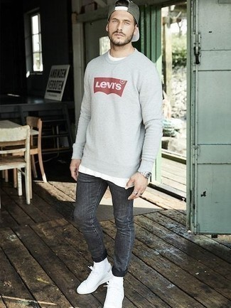 Charcoal Jeans Outfits For Men: Step up your off-duty style in a grey print sweatshirt and charcoal jeans. The whole look comes together if you add white canvas low top sneakers to this outfit.