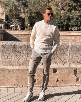 Light Blue Vertical Striped Long Sleeve Shirt Outfits For Men: If you prefer laid-back style, why not test drive this combination of a light blue vertical striped long sleeve shirt and khaki cargo pants? For times when this look is too much, play it down by slipping into a pair of beige athletic shoes.