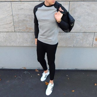 How to wear: grey sweatshirt, black sweatpants, white and black leather low top sneakers, black leather holdall
