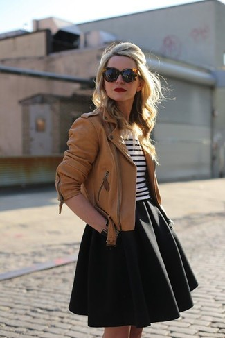 Let everyone know that you know a thing or two about style in a tan leather motorcycle jacket and a black full skirt.