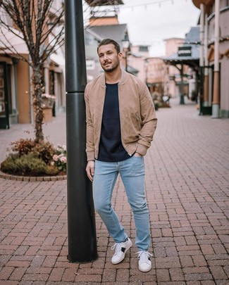 How to wear: tan suede bomber jacket, navy crew-neck sweater, light blue jeans, white low top sneakers