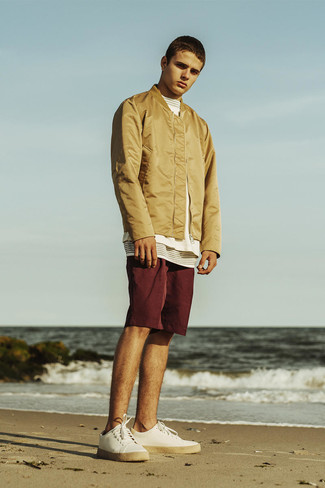 How to wear: tan bomber jacket, white and black horizontal striped crew-neck t-shirt, burgundy shorts, white canvas low top sneakers