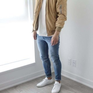 Blue Skinny Jeans Spring Outfits For Men: This off-duty pairing of a tan bomber jacket and blue skinny jeans is a surefire option when you need to look good but have no extra time. White canvas low top sneakers look wonderful here. So if you're after an outfit that's stylish but also feels totally spring-appropriate, this just might be it.