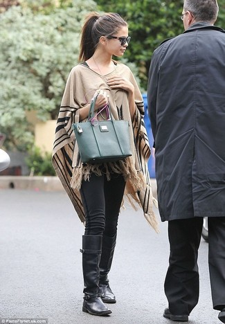 Selena Gomez wearing Tan Poncho, Black Leggings, Black Leather Knee High Boots, Dark Green Leather Tote Bag