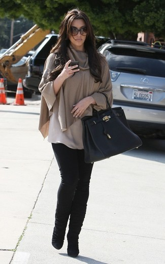 Kim Kardashian wearing Tan Poncho, Black Skinny Jeans, Black Suede Mid-Calf Boots, Black Leather Tote Bag