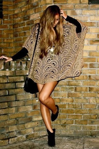 This off-duty pairing of a tan crochet poncho and a black sweater dress comes in handy when you need to look good but have zero time to spare. A pair of black suede ankle boots looks right at home paired with this look.