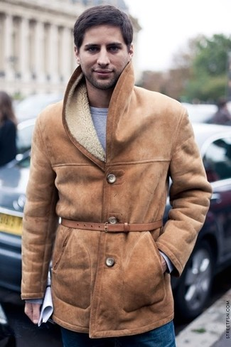 How to wear: tan shearling coat, grey sweatshirt, blue jeans, tan leather belt