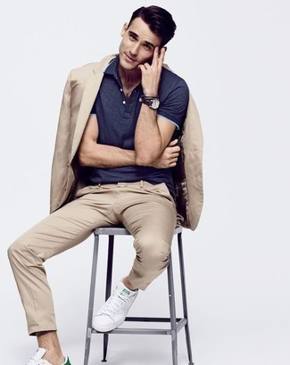 How to Wear a Navy Polo For Men: If the situation calls for a refined yet killer outfit, dress in a navy polo and a tan suit. Finishing with white leather low top sneakers is an effortless way to add a playful feel to this look.
