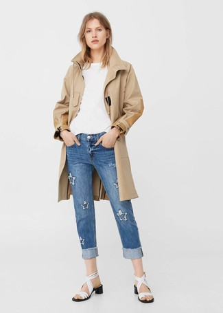How to wear: tan trenchcoat, white crew-neck t-shirt, blue embroidered jeans, white leather heeled sandals