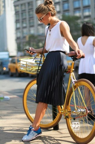 This combination of a white tank and a black pleated midi skirt is simple, totally chic and oh-so-easy to imitate! A good pair of sneakers are sure to leave the kind of impression you want to give. One actually can to remain fresh and absolutely chic under the unbearable heat, and this ensemble is a striking illustration of just that.