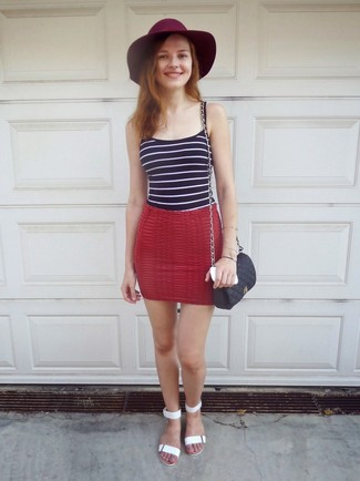A navy and white horizontal striped tank and a black cross body bag are a great outfit formula to have in your arsenal. Balance this ensemble with white leather flat sandals. As you can see here, this is a killer pick for hot weather.