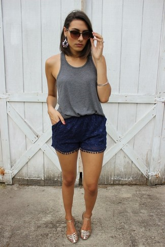 Pair a dark grey tank with dark blue lace shorts for a trendy and easy going look. Mix things up by wearing silver leather flat sandals.