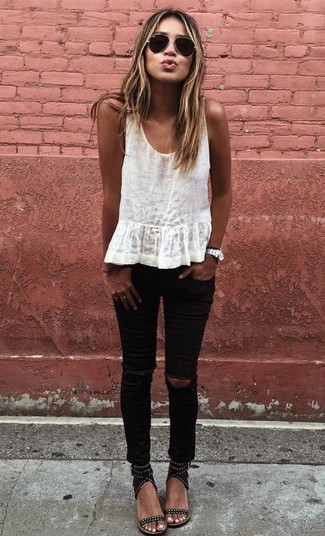 Try pairing a white tank with black ripped slim jeans to create a great weekend-ready look. A pair of black studded suede heeled sandals adds some real flair to this getup. We can't get enough of this outfit for summertime days.